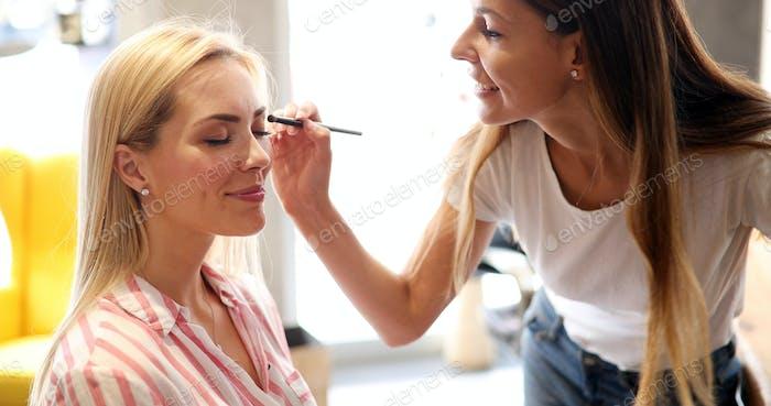 Makeup artist applies eye shadow. Perfect makeup