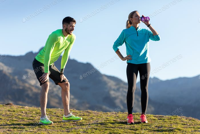 Healthy young couple relaxing after running while the woman drinks water on the mountain.