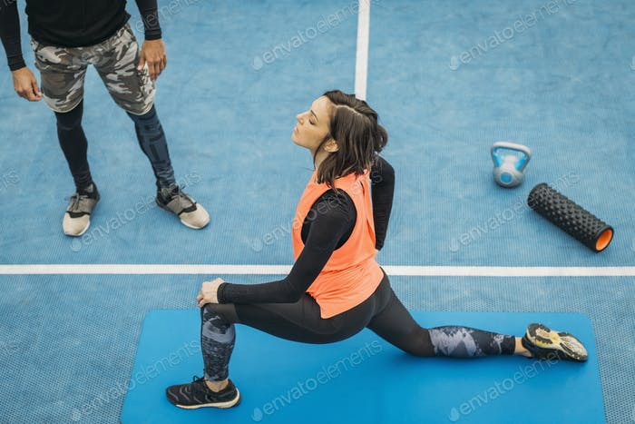 Stretching After Training, Young Woman with Fitness Coach, Outdoors