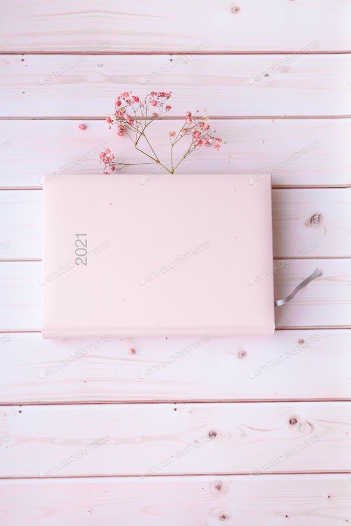 Diary pink organizer with cute pink dried flowers sign 2021 on white pink wooden background.