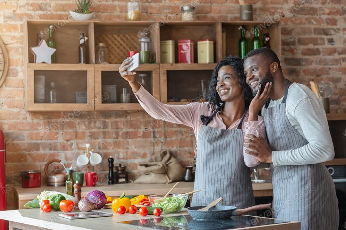 Happy married couple in kitchen taking selfie on smartphone