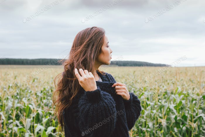 Beautiful carefree long hair asian girl in yellow hat and knitted sweater in autumn corn field