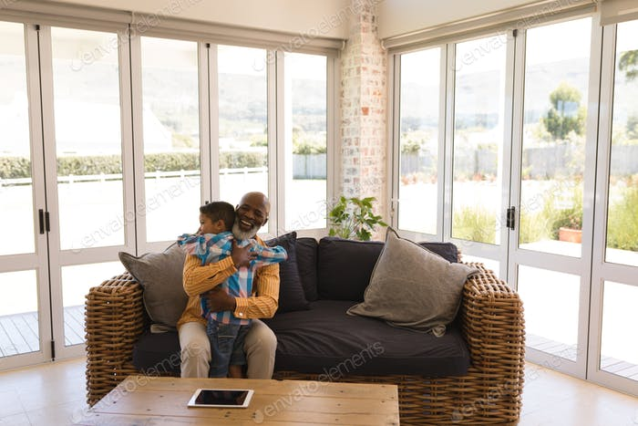 Grandfather and grandson embracing each other in living room at home