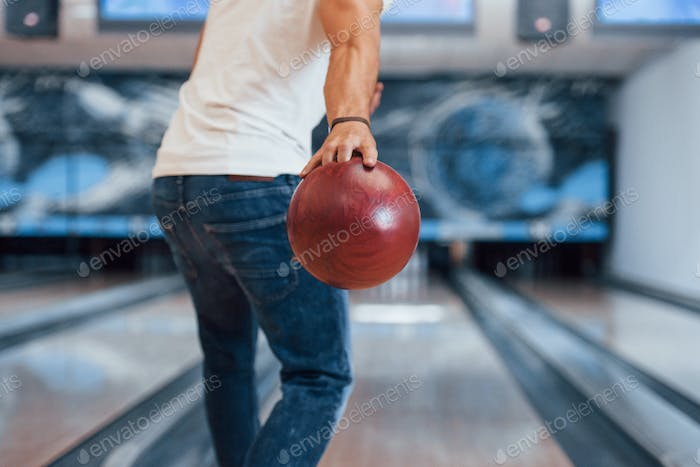 Weekend activities. Rear particle view of man in casual clothes playing bowling in the club