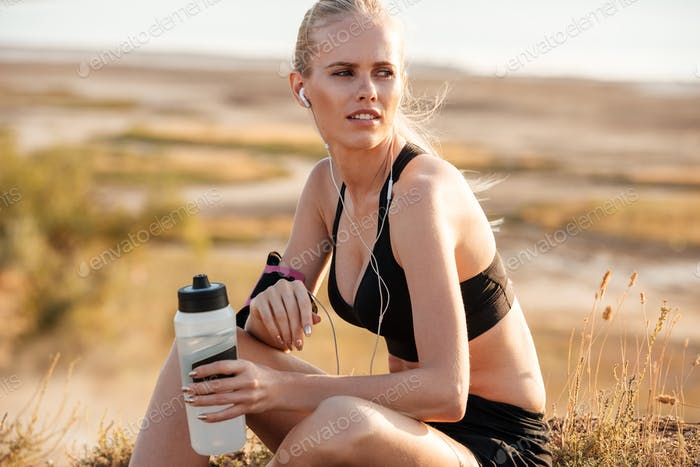 Fitness young woman resting and holding water bottle after training