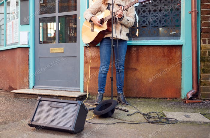 Nahaufnahme von weiblich musiker busking spielen akustische gitarre im freien in street