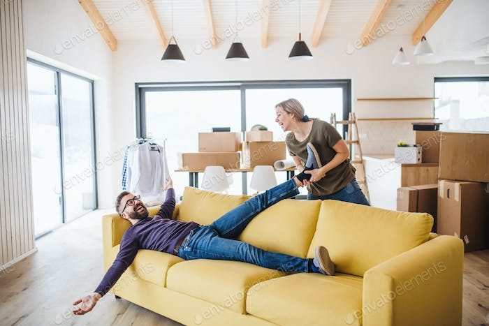 A young couple moving in new home, having fun.