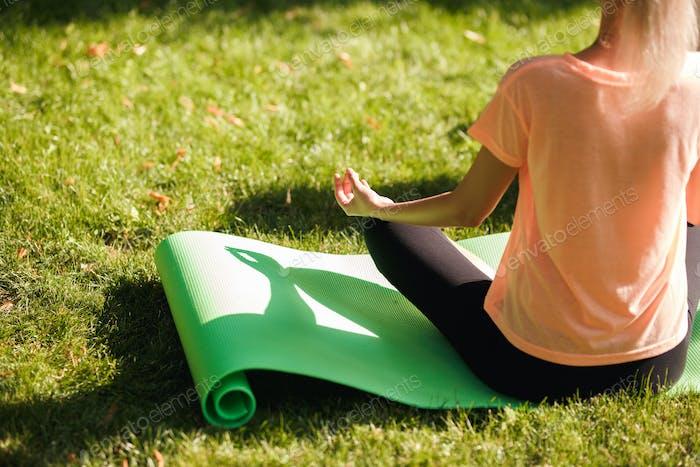 Вид сзади женщины, практикующей йогу сидит в положении лотоса. Концепция здорового образа жизни