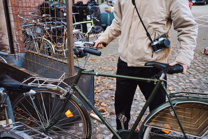 Close up young casual hipster man with retro bicycle on city street