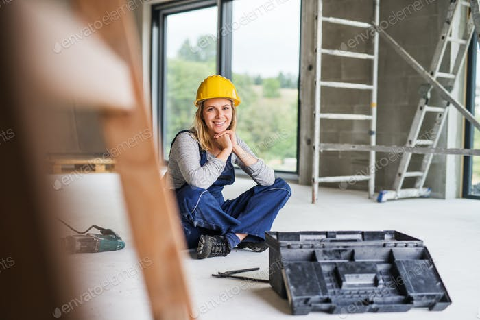 Young woman worker sitting on the floor on the construction site.