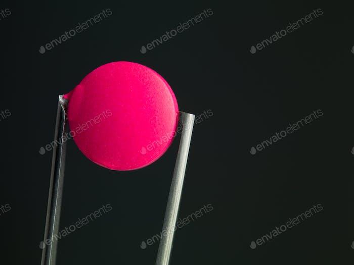pink pill in tweezers