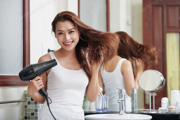 Cheerful ethnic woman with hairdryer in bathroom