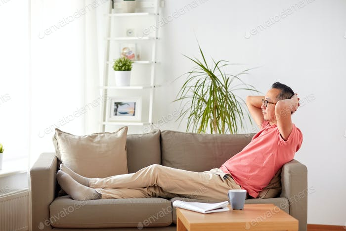 man in glasses relaxing on sofa at home