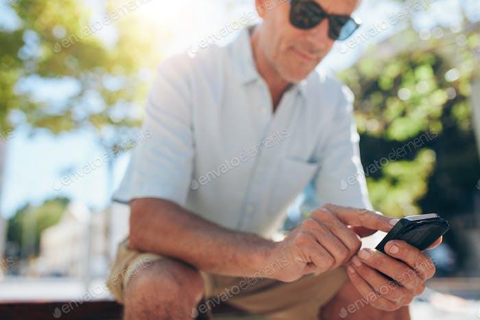 Senior Mann mit Handy im Freien