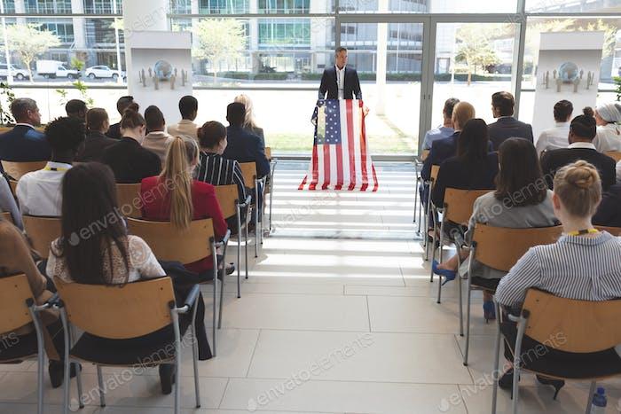 Gemischte Rasse Mann Sprecher in einem Business-Seminar im Bürogebäude mit amerikanischer Flagge sprechen