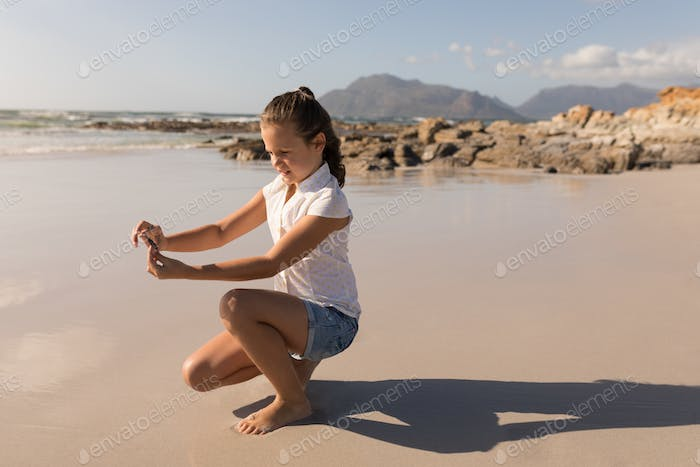 Side view of a little cute girl holding seashell on beach in the sunshine
