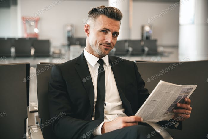Smiling businessman reading newspaper