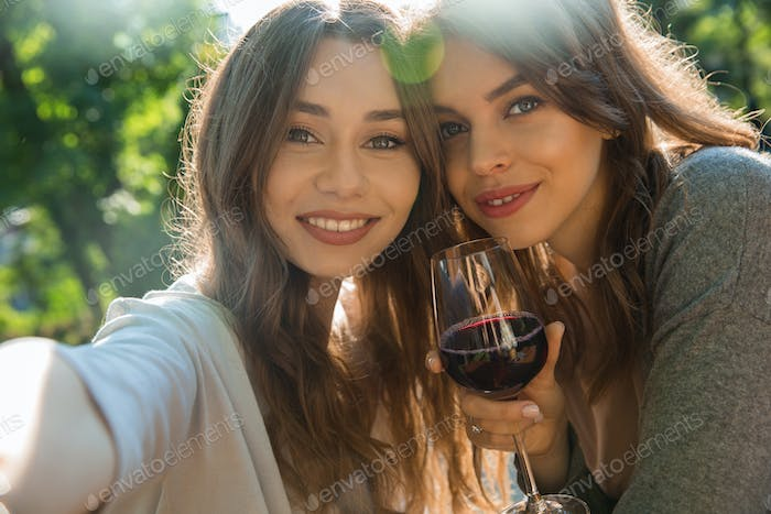 Cheerful young women outdoors in park drinking wine make selfie