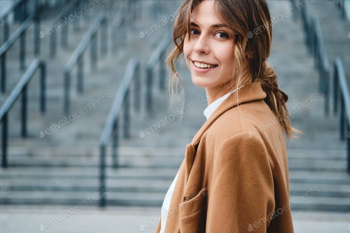 Portrait of young pretty stylish woman in coat dreamily looking in camera outdoor
