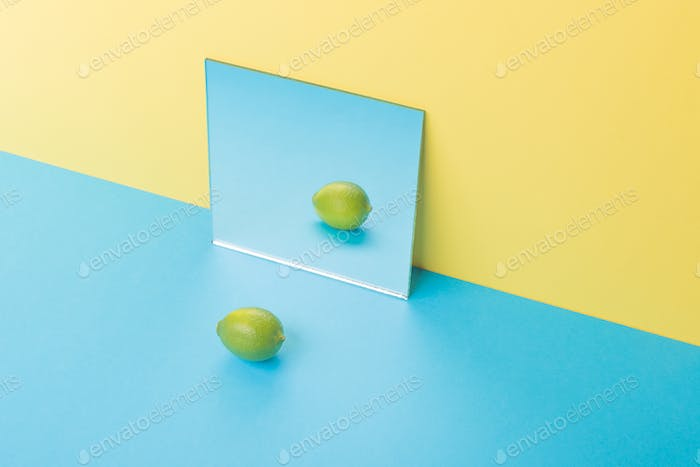 Lime on blue table isolated over yellow background near mirror