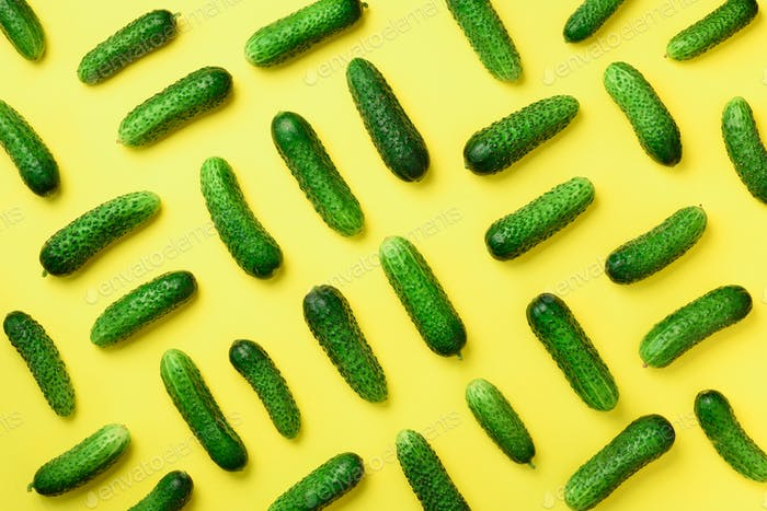 Creative pattern of fresh green cucumbers on yellow background. Top view. Copy space. Minimal design