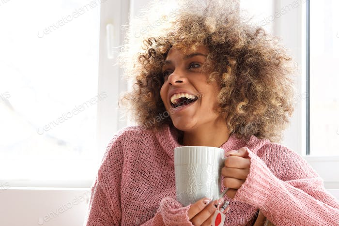 attractive young african american woman holding holding cup of tea