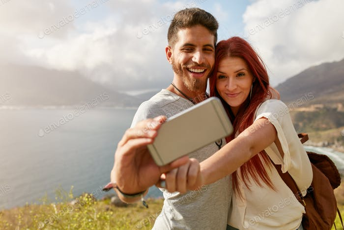 Young couple hiking taking selfie with smart phone