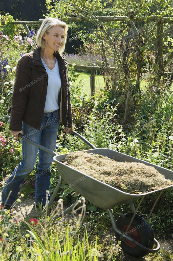 Eine Frau schiebt eine Schubkarre von Grasausschnitten.