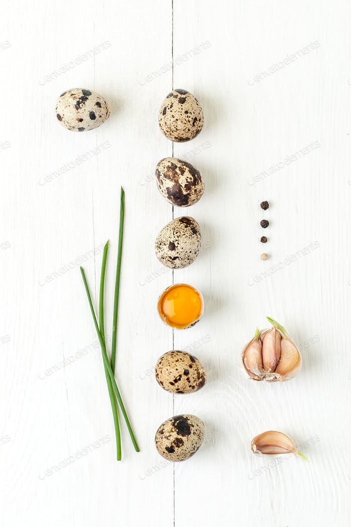 Minimalistic still life with quail eggs, garlic and shiny onion