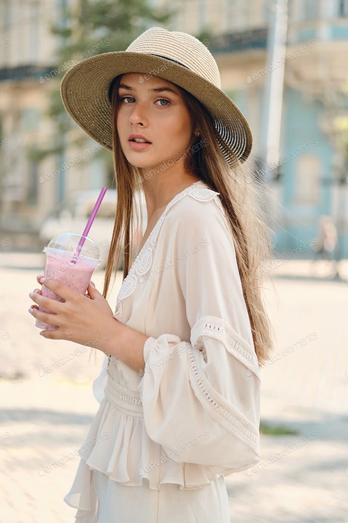 Young beautiful girl in dress and hat holding smoothie dreamily looking in camera on city street