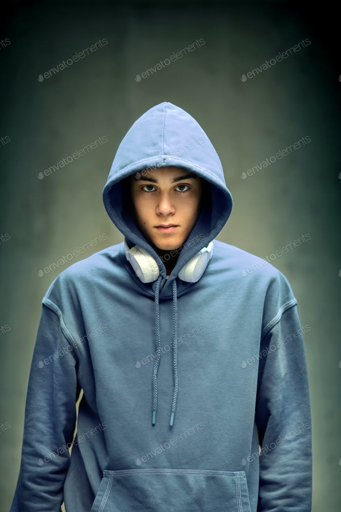 Moody serious teenage boy wearing a light blue hoodie