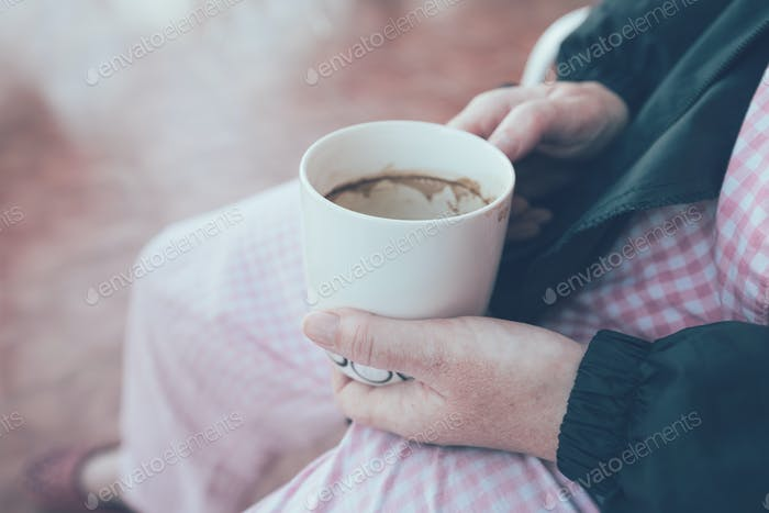 Hospital patient holding cup and drinking coffee