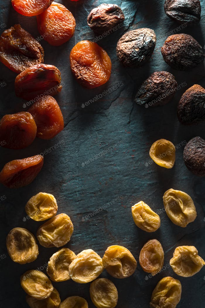 Frame of brown, orange, yellow dried apricots on a gray stone