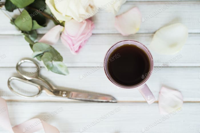 Closeup of cup of tea and roses
