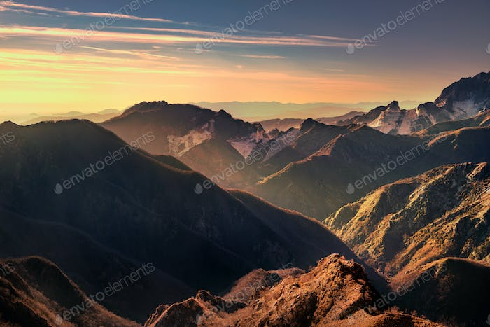 Alpi Apuanei mountains and marble quarry view at sunset. Carrara