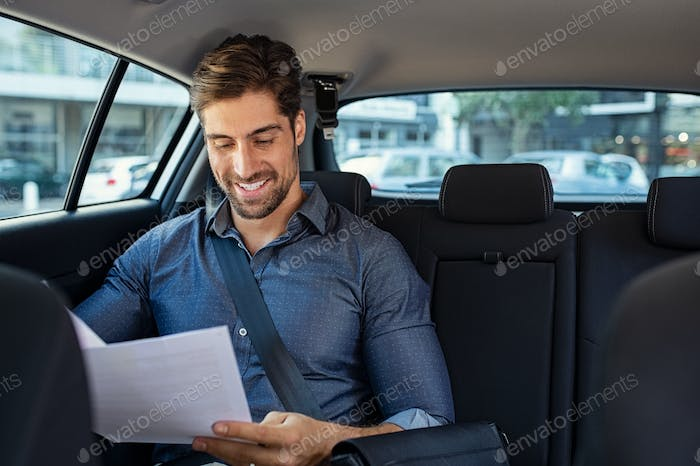 Businessman reading documents in car