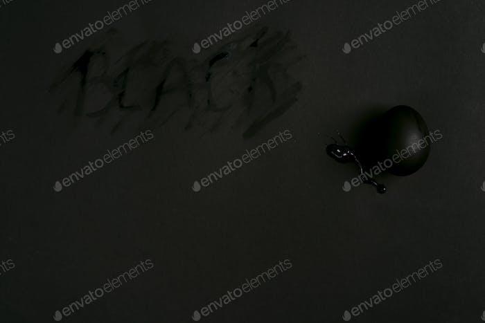 Schwarz bemalte Eierdekoration auf dem gleichen Farbhintergrund