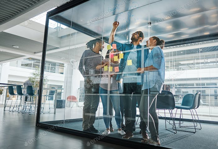 Diverse businesspeople brainstorming together on a glass wall