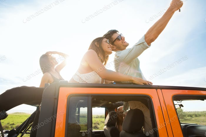 Group of happy young people taking selfie with smartphone