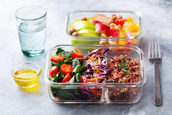 Lunchbox mit Gemüse, braunem Reis und Obstsalat. Gesundes Essen. Grauer Hintergrund.