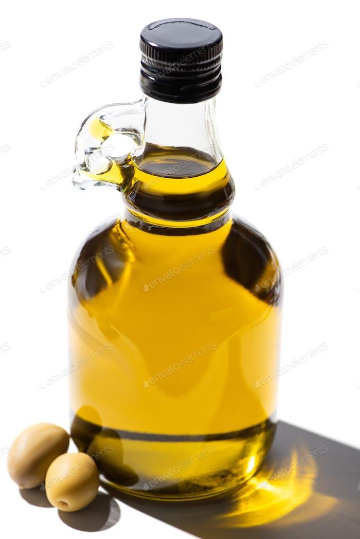 Olive Oil in Bottle Near Green Olives on White Background