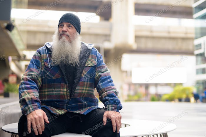 Mature handsome bearded man thinking and sitting in the city outdoors
