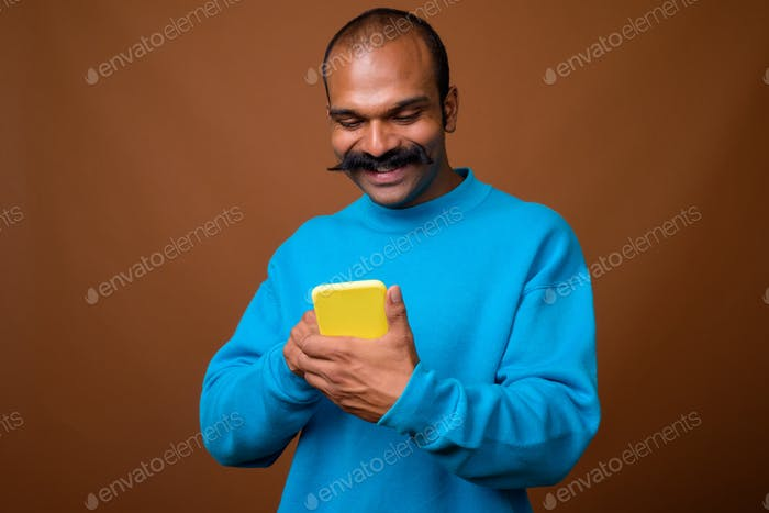 Portrait of happy Indian man with mustache using phone