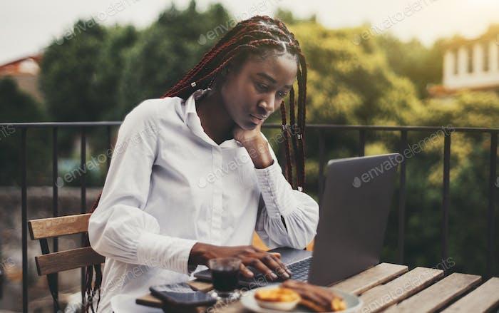 Африканская женщина-фрилансер с ноутбуком