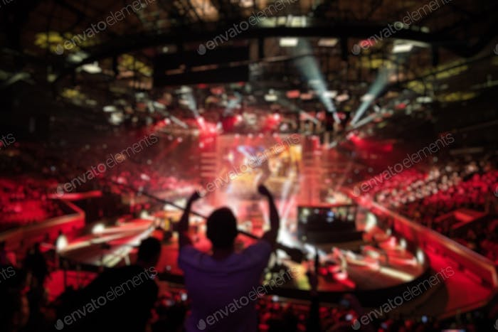 Abstract blurred background of big esports gaming event at big arena. Man with a hands raised