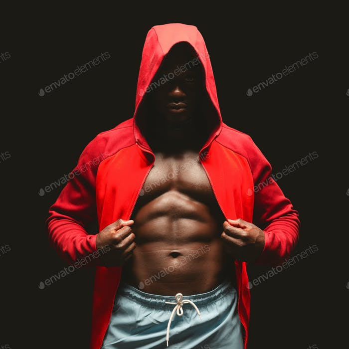 African american boxer in red hoodie over black studio background
