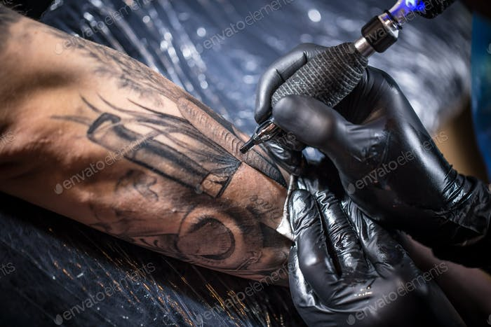 Hands of the artist tattooing