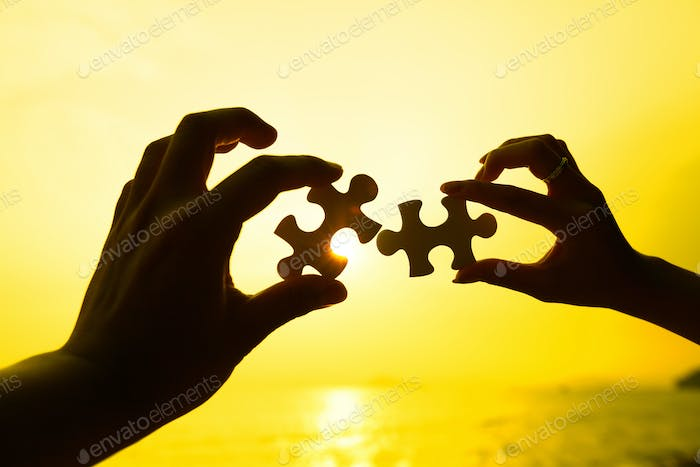 Two hands trying to connect puzzle pieces with sunset background