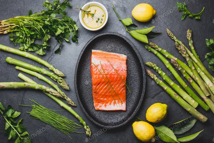 Ingredients for cooking - salmon, asparagus herbs ang lemon.