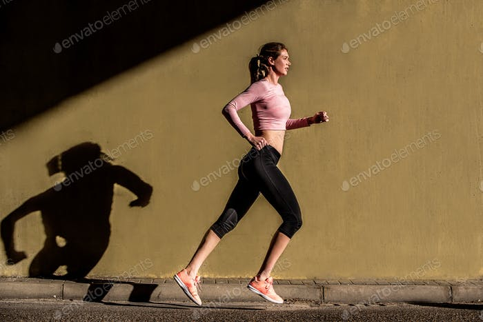 Young fit blonde woman running in the street